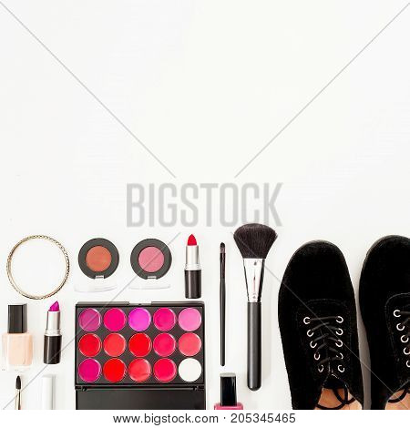 Feminine desk with woman cosmetics, accessories and shoes on white background. Flat lay, top view. Beauty background