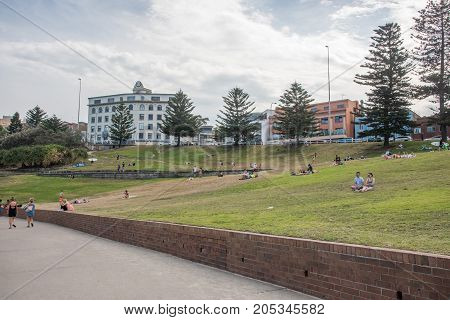 SYDNEY,NSW,AUSTRALIA-NOVEMBER 21,2016: Bondi Beach foreshore with grass area, tourists and local architecture on a cloudy day in Sydney, Australia