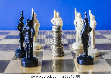 Coins Are Stacked On A Chessboard Surrounded By Black And White Chess Pieces