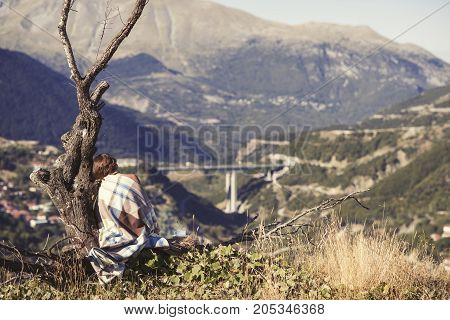 A girl wrapped up in a plaid sitting on a tree with a cup of coffee and looking at the city. A girl in a plaid opposite the village of Metsovo in Greece
