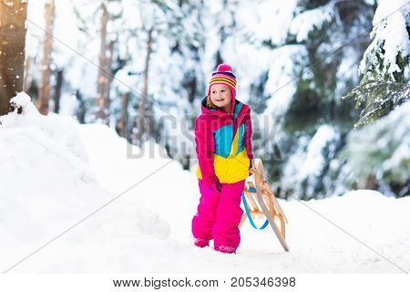 Child Playing In Snow On Sleigh In Winter Park