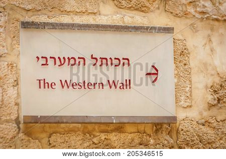 A direction sign board to the Western wall in Hebrew and English somewhere in the street of the Old city Jerusalem.