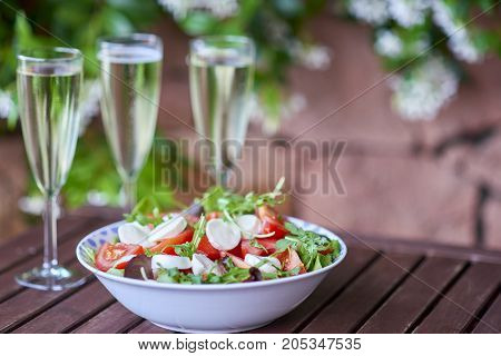 Three glassed of champagne and fresh salad - close up