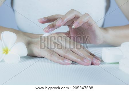 hand of woman apply lotion on skin of back hand with lotion bottle isolated on white background.