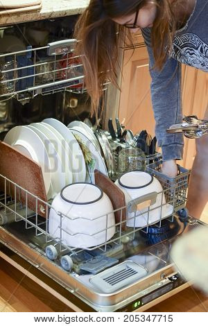 Woman Loading Dishes And Silverware Into Dishwasher