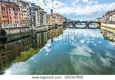 Old buildings and beautiful Ponte Santa Trinita mirrored in the river Arno Florence Tuscany Italy. Travel destination.