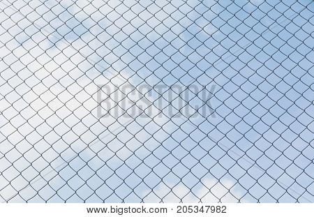 Rusty chain link fence under the sky background. Abstract closeup of a chain link sky background.