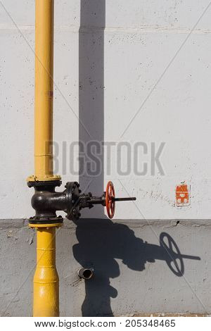 Yellow Industrial gas pipeline with black valve and a shadow on the wall