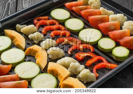 Variety of vegetables prepared for cooking on grill pan. Vegetables are cut into pieces and laid in rows. Cooking of dietary vegetarian dishes. Concept of healthy food