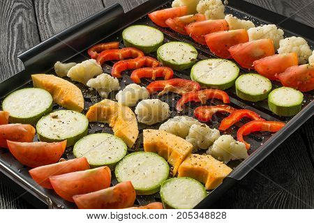 Variety of fresh vegetables prepared for cooking on grill pan. Vegetables are cut into pieces sprinkled with salt and spices laid in rows. Prepare diet vegetarian dishes. Healthy food concept