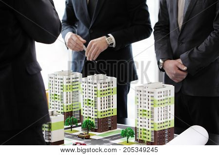 Business meeting of architects and investors looking at model of residential quarter houses poster