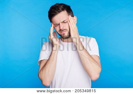 Stressed European man with beard and mustache frowning his face holding hands on head having depression not knowing what to do suffering from headache having some serious problems in his life.