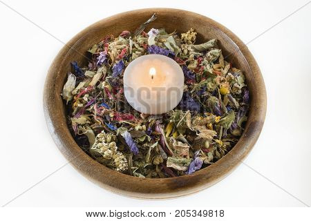 Wooden bowl with potpourri of dried flowers and candle.