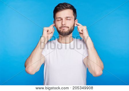 Young bearded man having discontent look closing eyes plugging ears being annoyed with noise wanting silence calm atmosphere being exhausted of loud sound and shouting. Studio shot on blue wall.
