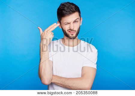 Isolated portrait of European young international student tired from passing exams shooting himself with finger gun gesture against blank blue wall background. Human face expressions and emotions.