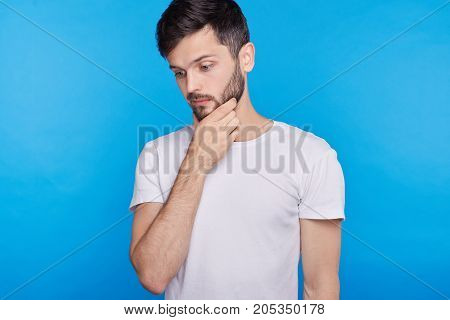 Studio portrait of young handsome man having concentrated thoughtful expression frowning keeping hand on his chin as if trying to remember something or making decision on blue wall background.