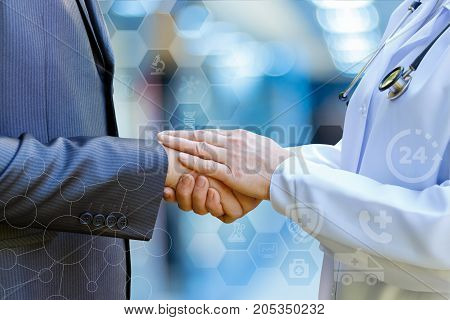 Doctor supports the patient's arm on blurred background.