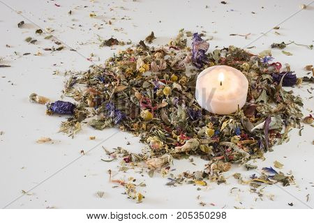 Flower potpourri on table with lit candle.