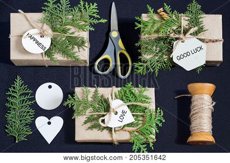 Homemade gift box decoration for Christmas. DIY hobby. Gift boxes are wrapped in kraft paper tied with twine with twigs of thuja and tags with wishes of happiness love good luck. Top view flat lay