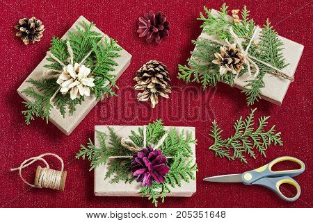 Homemade gift box decoration for Christmas. DIY hobby. Boxes are wrapped in kraft paper tied with twine with branches of thuja and pine cones. Original gift decoration