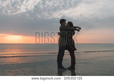 young loving couple hugging on the seashore in autumn.