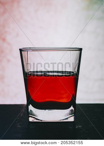 Red alcohol coctail in glass on bar table
