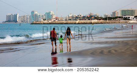 Family walks on beach with Salinas Ecuador skyline in the background on Nov 23 2012