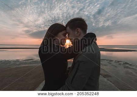 young loving couple hugging on the seashore sunset in autumn.