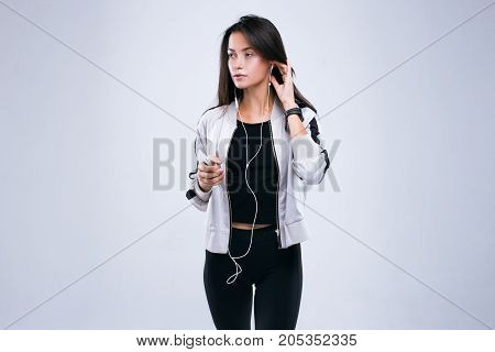 Casual sport woman starts training with earphones and mobile telephone in her hands. Standing in studio isolated over gray background