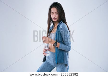 Beautiful fitness woman posed with bottle of water in earphones. Rest after training and drinking water.