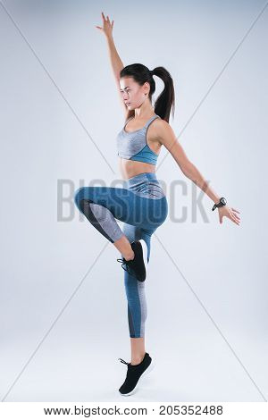 Full length portrait of a young healthy woman in sportswear posing and jumping with hands up, isolated over gray background