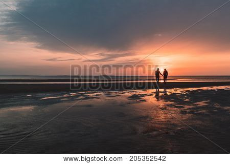 young loving couple on the beach at sunset in autumn