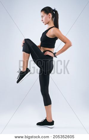 An attractive sportswoman stretching leg while standing isolated over gray background and looking away