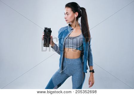 Beautiful woman in sport wear posed with bottle of water and listening to music in earphones while standing isolated over gray background