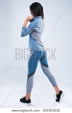 Beautiful strong back of woman. Girl dresses hood sportswear and listening to music in earphones while standing isolated over gray background.
