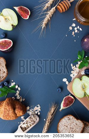 Breakfast with croissant bread apple figs oatmeal on a gray background. View from above