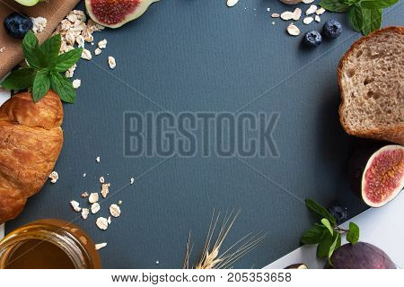 breakfast with croissant oatmeal honey bread and figs on a gray background. View from above