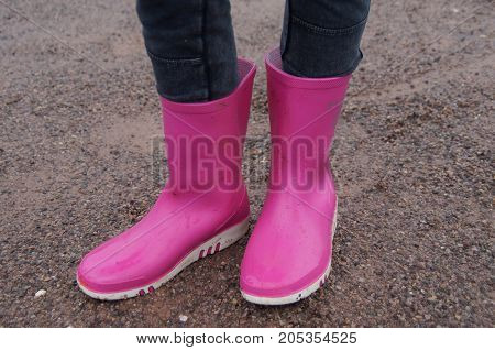 Girl standing in pink rubber Dunlop child rain boots.