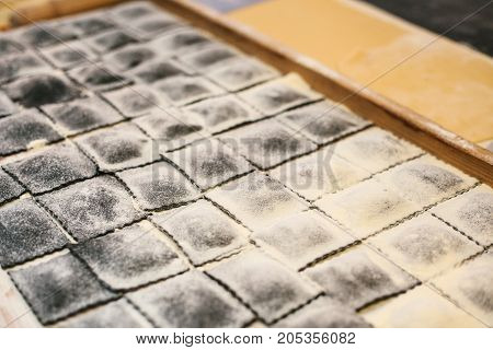 Preparation of Italian dish Ravioli. This is pasta from dough with different fillings. An analog of ravioli is dumplings. Kitchen background. National Food. Unprepared.