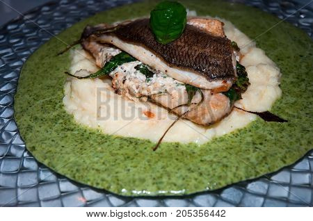 2 pieces of sea bream fillet stuffed with feta and caramelized onions, on a bed of mashed potatoes and creamy spinach cream .