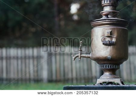 Vintage metal copper tea samovar on nature background. Samovar side view.