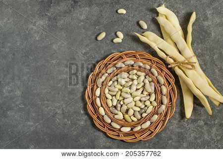 Bunch of white string beans tied with twine and bean grain on round wicker tray. Long white pods and tray on gray textured background. New harvest. Ingredient in healthy and dietary food. Top view