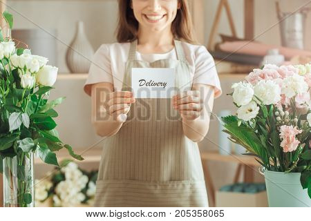 Young female florist working with flowers delivery