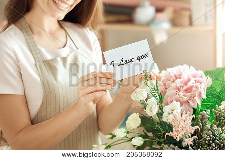 Young female florist working with flowers making bouquet