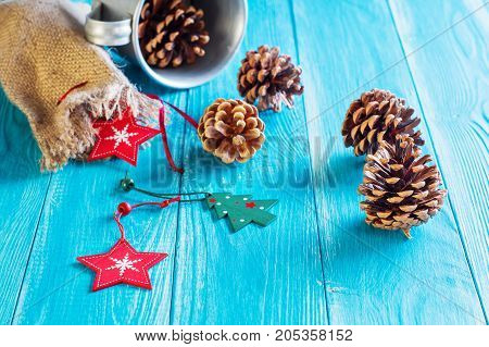 Christmas background. Fir cones gift bag and red wooden stars on blue wooden background with copy space. Christmas or New Year card template.
