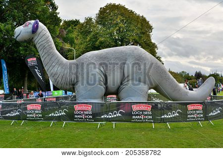 Inverness, United Kingdom - September 23, 2017. Inflatable Nessie, at the finish line of Loch Ness Marathon 2017, with people.