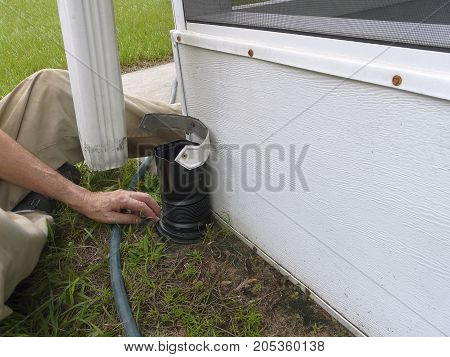 A man is installing a connector between the downspout and drainage pipe on his house to seal out debris and prevent foundation damage from water.