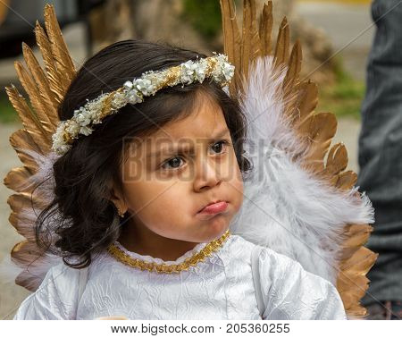 The  Reluctant Angel With A Pout At The Pase De Nino Parade
