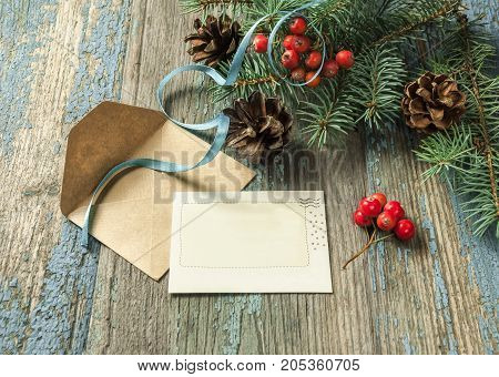 Christmas card: empty paper form with fir-tree branches on old wooden background, copyspace