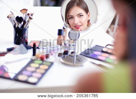 Young beautiful woman making make-up near mirror, sitting at the desk.